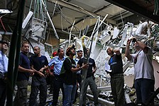 Firefighters and police survey damage at the Hutzot Shopping Center in Ashkelon. (AP)
