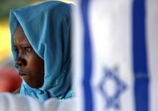 July 11, 2007: A Sudanese refugee stands behind an Israeli flag at a park near the Israeli Parliament building in Jerusalem, during a rally asking the Israeli government for assistance. (AFP)
