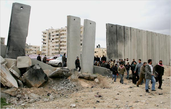 Palestinians breaking through the Egyptian apartheid wall. (AP)