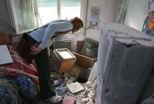 A woman inspects damage to a nursing home in northern Israel after it was hit by a Katyusha rocket yesterday. (AFP/Getty)