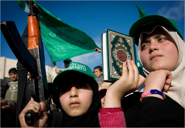 A Palestinian girl holds a Koran and a fake rifle at a recent rally organized by Hamas in Gaza. (New York Times)